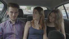 Millennial pasażerów przyjaciele opowiada opowieści i mówi podczas podróżnego uber samochodu na miastowej drodze - zbiory wideo