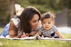 Millennial Spaanse moeder die op een deken in het park met haar baby liggen die, sluit omhoog glimlachen stock fotografie