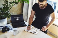 Student writes with pen in notebook while looking at smartphone. On table laptop with inscription on screen- e-learning royalty free stock photo