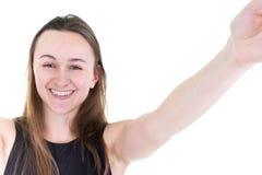 Millennial tonårs- flicka i svart ta en selfie på mobiltelefonen i vit bakgrund royaltyfria foton
