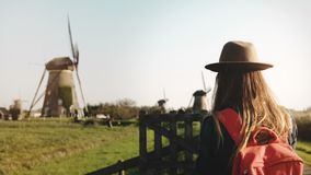 Millennial tourist girl takes a photo of windmill. Traveler woman in hat with red backpack enjoys pastoral scenery. 4K. Millennial tourist girl takes a photo of stock video