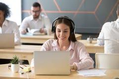 Millennial uśmiechnięty bizneswoman jest ubranym hełmofony pracuje na l zdjęcia stock