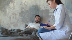 Millennial verpleegster die diagnose maken terwijl het bezoeken van patiënt stock videobeelden