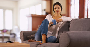 Millennial white woman poses on her couch holding her coffee Stock Images