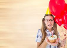 Millennial woman with balloons and cupcake against blurry cream background Stock Photo