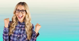Millennial woman celebrating against blurry blue background Royalty Free Stock Images