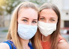 Free Millennial Woman Friends Taking Selfie Smiling Behind Face Masks - New Normal Summer Friendship Concept With Young Girls Having Stock Image - 193859011