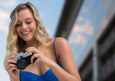 Millennial woman looking down at camera against blurry building. Digital composite of Millennial woman looking down at camera against blurry building Stock Photography