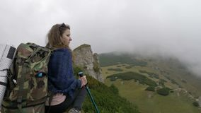 Millennial woman on mountain standing high on cliff looking the distant beautiful landscape with misty hills peaks and forests -. Millennial woman on mountain stock footage