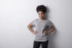 Millennial woman posing indoors. Gray shirt Stock Photos