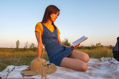 Young lady with book on rug resting on nature and reading book at sunset