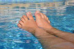 Summer vibes, feet in swimming pool, keeping cool stock image