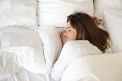 Millennial woman sleeping well on soft pillow, top view. Millennial woman sleeping well on soft pillow and comfortable bed mattress with white cotton sheets royalty free stock photos