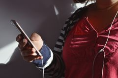 Millennial woman using smart phone with headphones, indoors stock image