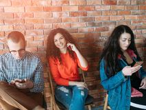 Millennials creative workspace modern devices. Millennials business life. Young people working in loft workspace, using smartphones. Modern devices advantages stock images