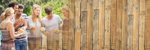 Millennials die en bij bbq met houten paneelovergang lachen eten Royalty-vrije Stock Fotografie