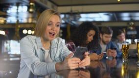 Millennials gebruikend cellphones in bar, aan sociale netwerken wordt gewijd, vrij WiFi dat stock videobeelden