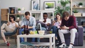 Millennials gebruikend smartphones thuis genietend van sociale media die Internet surfen stock footage