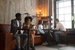 Millennials multiraciaux appréciant le café travaillant aux instruments dans la Co Image libre de droits