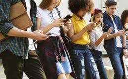 Millennials in openlucht gebruikend smartphones diversiteit stock foto