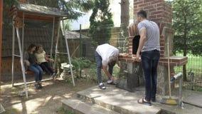 Millennials pojkar och flickavänner som tillsammans samlas i trädgården som förbereder gallret för grillfestparti - stock video