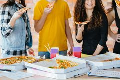 Millennials routine unhealthy junk food habit. Millennials routine. Cropped shot of young coworkers eating pizza during lunch break. Junk food habit. Unhealthy royalty free stock photos