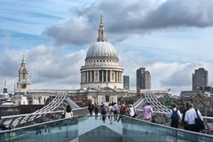 Millennium Bridge in London. Commuters walk across the Millennium Bridge in London on July 1, 2013. On the background is St Paul's Cathedral. The bridge was Royalty Free Stock Images