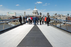 Millennium Bridge and St Pauls in Summer. LONDON, UK - MAY 13, 2015: Tourists and commuters walk on the Millennium bridge with St Pauls in the background on a Royalty Free Stock Photography