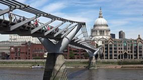 Millennium Bridge on Thames River with St Paul Cathedral of London in background stock video footage