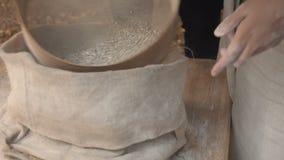Miller distingue la farina integrale Una donna vaglia il grano al un setaccio del woode che lo separa dalla farina a terra stock footage