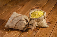 Millet in bags on a wooden table Stock Image