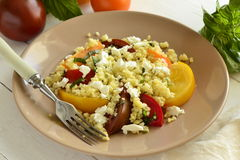 Millet with basil and fresh tomatoes, goat cheese Stock Image
