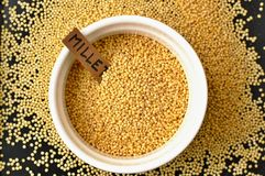 Millet in the bawl with the label on the black background Royalty Free Stock Photo