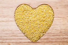 Millet groats heart shaped. Dieting concept. Millet groats heart shaped on wooden surface. Healthy food help lower cholesterol Royalty Free Stock Photography