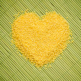 Millet groats heart shaped on green mat surface. Royalty Free Stock Photo