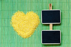 Millet groats heart shaped on green mat surface. Stock Photos