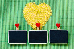 Millet groats heart shaped on green mat surface. Royalty Free Stock Images