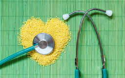 Millet groats heart shaped on green mat surface. Stock Images