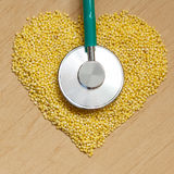 Millet groats heart shaped on wooden surface. Royalty Free Stock Photography