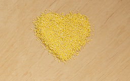 Millet groats heart shaped on wooden surface. Royalty Free Stock Photos