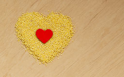 Millet groats heart shaped on wooden surface. Stock Image