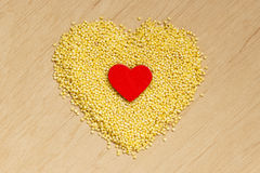 Millet groats heart shaped on wooden surface. Stock Photography