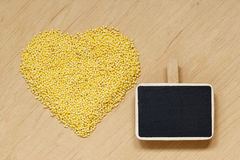 Millet groats heart shaped on wooden surface. Royalty Free Stock Image