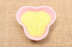 Millet groats in pink bowl on jute canvas Stock Photo
