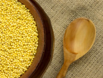 Millet groats in a round pot. And wooden spoon Stock Photography