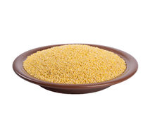 Millet heap on plate angle view. Millet heap on plate isolated on white backgrpound high angle view Royalty Free Stock Photography