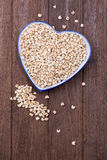 Millet in heart shape bowl Stock Images