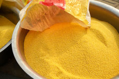 Millet in the metal basin. Into the metal bowl of golden millet Stock Images