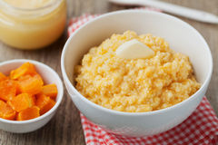 Millet porridge with baked pumpkin and butter in bowl on wooden table Royalty Free Stock Photo