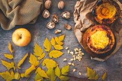 Millet porridge baked in pumpkin, walnut, seeds, apple, yellow leaves, warm sweater Stock Photos
